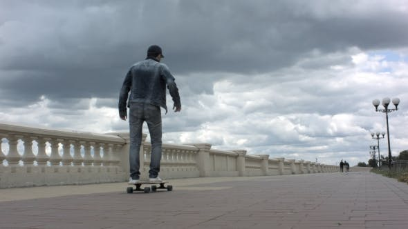 Cover Image for Young Man Riding a Skateboard In Cloudy Day.