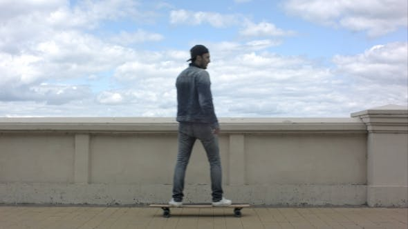 Thumbnail for Young Man Appearing In The Frame And Riding a Skateboard In Cloudy Day.