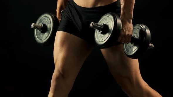Sportler mit nacktem Torso macht Kurzhanteln Kniebeugen.