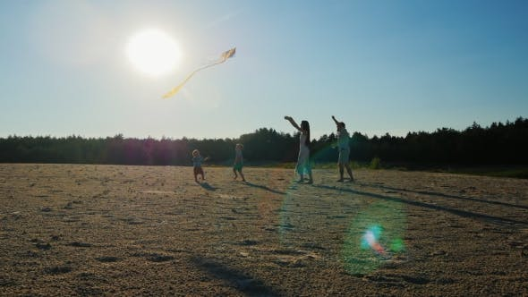 Thumbnail for Young Family - Mom, Dad and Two Sons are Playing With a Kite