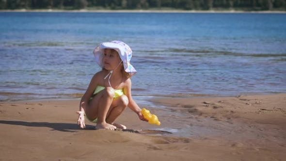 Thumbnail for Cute Little Blonde Girl Playing With The Sand At a Lake