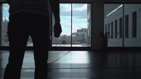Thumbnail for A Man In The Lobby Of The Office Building With Tall Windows, Is Coming To The Window