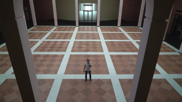 Thumbnail for Middle-aged Man Standing In a Large Circle With Columns, Talking On The Phone.
