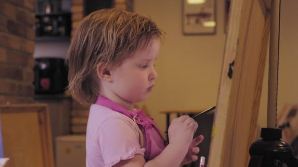 Thumbnail for The Little Girl Paints On a Canvas In The Studio And Smiling.