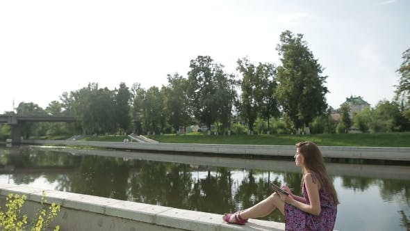 Young Woman Write Something In Her Notebook On River Bank In City Park