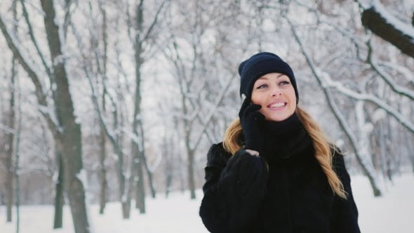 Thumbnail for Young Attractive Woman Talking On The Phone In a Winter Park, Smiling