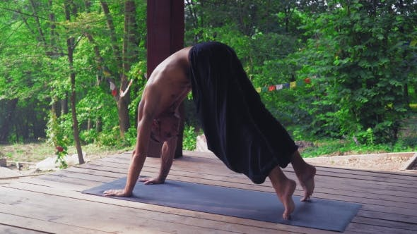 Thumbnail for Man Performs Yoga Exercises While Standing On a Platform In The Forest.