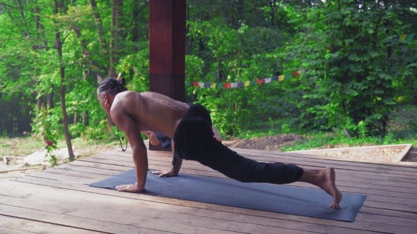 Thumbnail for Man Performs Yoga Exercises, Lifting One Leg And Bending The Other.