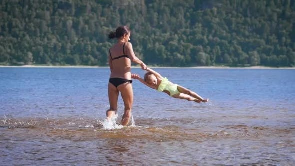 Thumbnail for Mother Playing Turning Around Her Baby Girl Daughter In The Park Lake