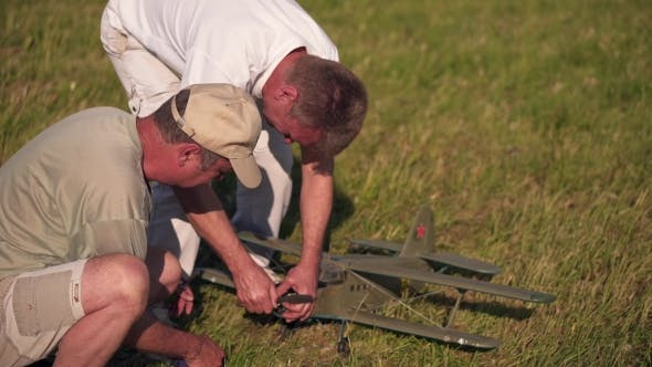 Cover Image for Two Men Tuning Model Aircraft In Hands