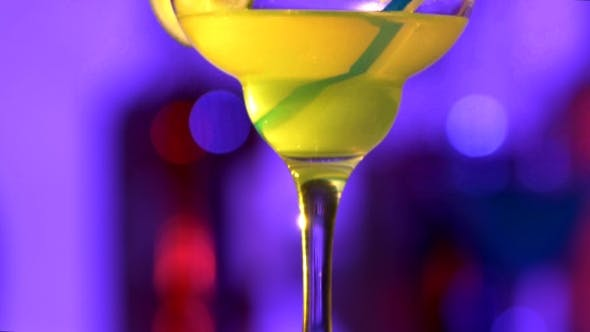 Thumbnail for Green And Yellow Cocktail With Lemon Decortion And Coconut On Edge