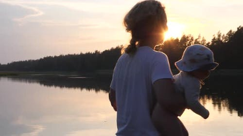 Happy Young Mother Holding and Spinning Her Baby Twins at Sunset. Lake and Trees on the Background