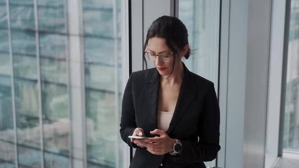 Thumbnail for Portrait of an Attractive Businesswoman with a Smartphone in Her Hands in a Modern Office