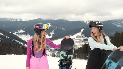 Two Stylish Women with Their Snowboards on Mountain