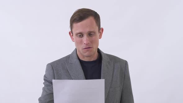 Cover Image for Portrait of Pleasant Man Reading Text Written on Piece of Paper Very Emotionally
