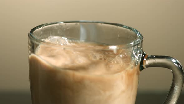 Thumbnail for Milk poured into coffee in ultra slow motion