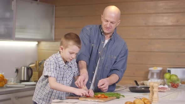 Thumbnail for Proud Father Encouraging Son Cutting Cherry Tomatoes in Kitchen