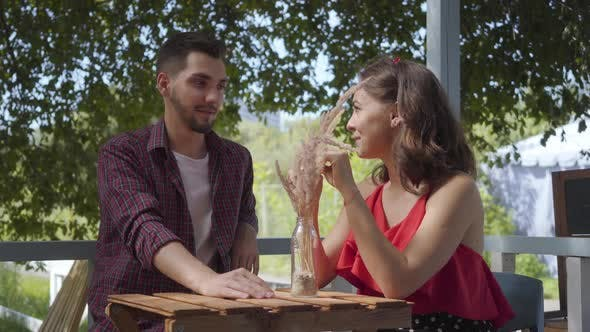 Young Happy Couple Sitting Outdoors at the Small Table Talking and Smiling To Each Other