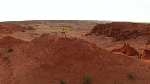 Thumbnail for Aerial View of a Man in a Canyon in the Gobi Desert at Sunset. Drone Footage
