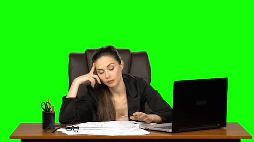 Une femme fatiguée lit un document comparant des informations avec un ordinateur portable, et le papier froissé, écran vert