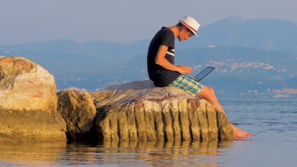Cover Image for Freelancing Guy Working Near the Rocks and the Sea. Business Man on Vacation in a Tropical Desert