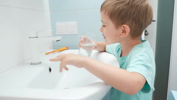 Portrait of Smiling Toddler Boy Rinsing Mouth with Water From Glass After Brushing and Cleaning