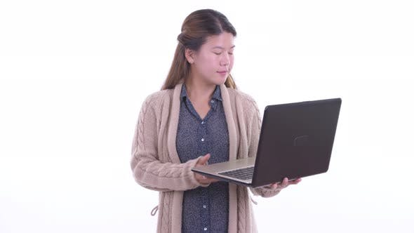 Thumbnail for Happy Young Asian Woman Talking While Using Laptop Ready for Winter