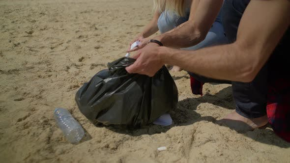 Thumbnail for Cropped Shot of Couple Picking Garbage on Beach