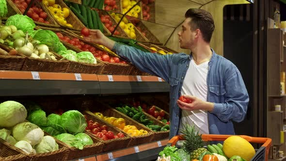 Thumbnail for Man Takes Tomatos and Cucumber From the Rack at the Supermarket