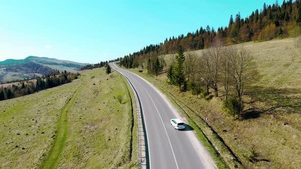 Aerial View White Car Travels in Beautiful Mountainous Terrain