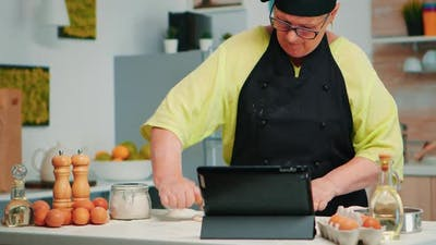 Woman Chef Using Tablet in Kitchen