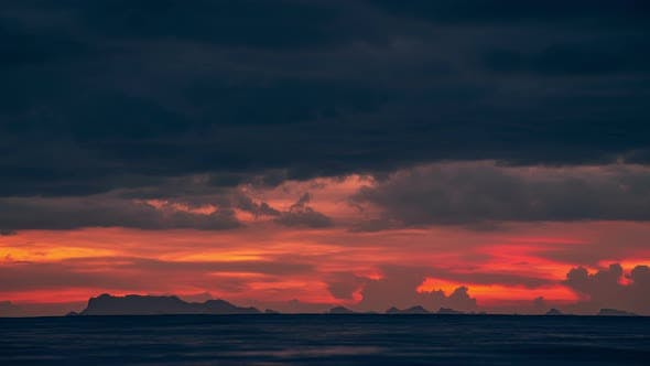 Cover Image for Sunset Over the Sea and Dramatic Cloudscape with a View of the Mountains Surat in Thani