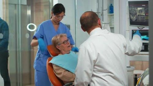 Nurse Putting Dental Bib to Old Woman
