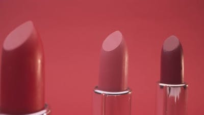 Three Lipsticks on Red Background