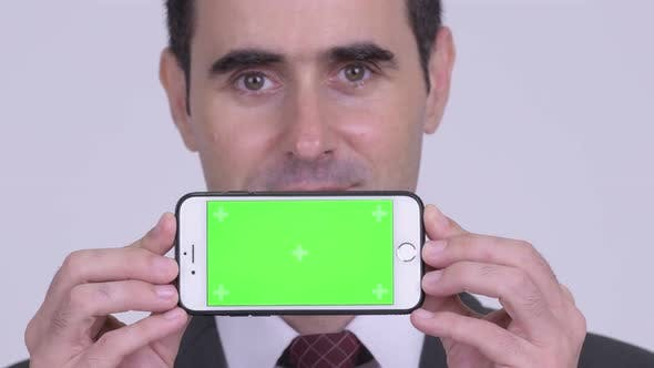 Thumbnail for Closeup of Happy Handsome Businessman Showing Phone