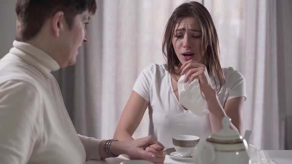 Thumbnail for Close-up Portrait of Beautiful Young Caucasian Girl Crying and Senior Brunette Woman Pouring Tea