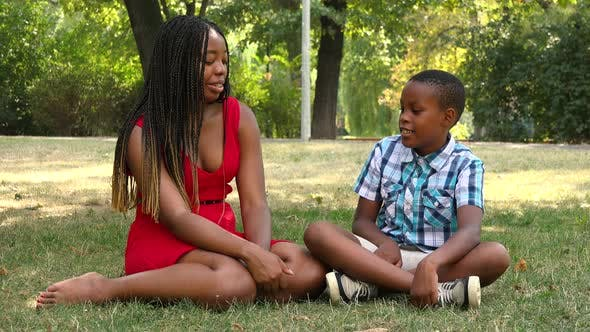 Thumbnail for A Young Black Mother and Her Son Sit on Grass in a Park and Talk