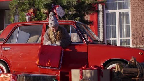 Surprised Teen Girl Holding Big Gift Box with Ribbon, Popping in Car Window Under New Year Tree