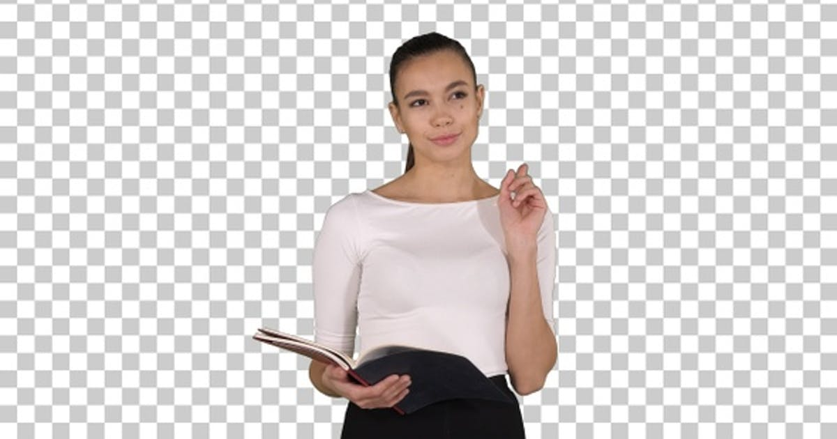 Young business woman walking and reading from notebook