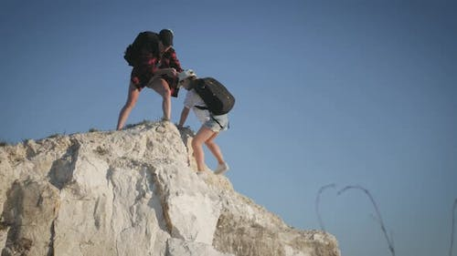 Girl Helps Her Friend Climb Up the Last Section of Mountain, Tourists with Backpacks Help Each Other