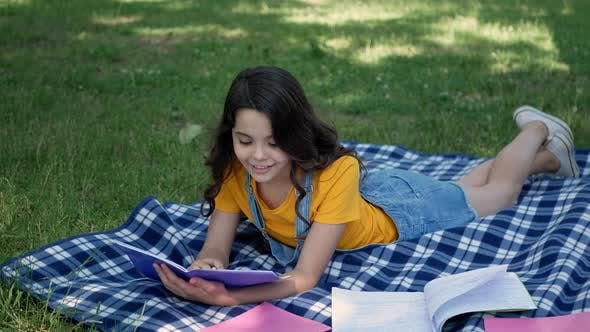 Thumbnail for Beautiful, little girl resting outdoors, lying on a plaid in a square