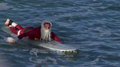 Santa Claus paddles out to go surfing.