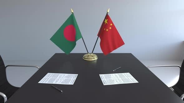 Flaggen von Bangladesch und China und Papiere auf dem Tisch