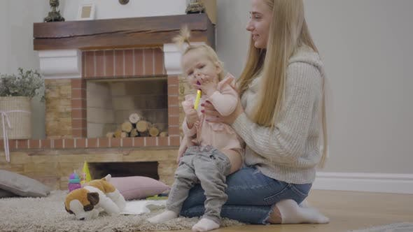 Young Caucasian Woman with Long Hair Putting Jeans on Cute Baby Girl and Taking Party Whistle Off