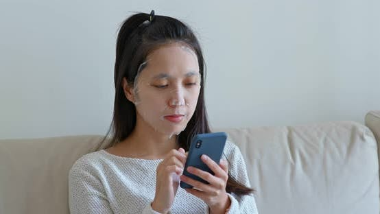 Thumbnail for Woman use paper mask with cellphone at home