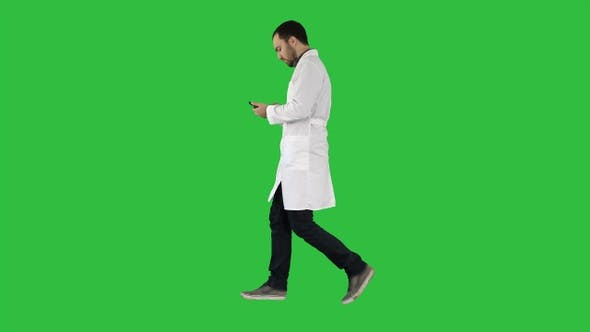 Cover Image for Male doctor walking and using mobile phone on a Green Screen