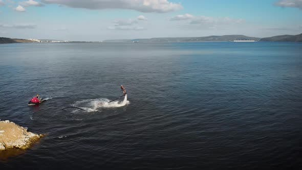 Thumbnail for Sportsman Is Flying on Flyboard on Lake in Daytime, Performing Trick, Aerial Moving Around View