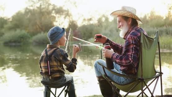 Thumbnail for Senior Großvater und sein fröhlicher kleiner Enkel, der auf dem Teich angeln und heißen Tee genießen