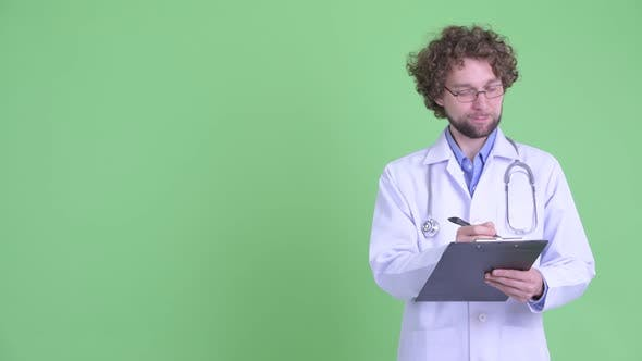 Cover Image for Happy Young Bearded Man Doctor Presenting Something While Writing on Clipboard