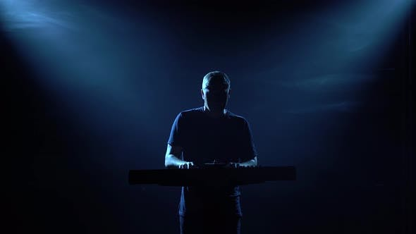 Musician Silhouette Playing on Synthesizer Piano Keyboard in Dark Studio with Neon Lighting